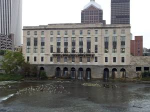 Water from the millrace spills out from beneath the Rundel building and back into the Genesee.