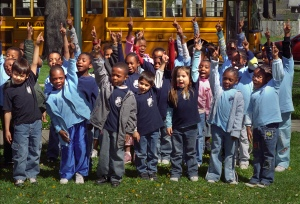 A group of children raise their hands in the air as part of an Arbor Day celebration at Susan B. Anthony Park, April 2006. From the collection of the Rochester City Hall Photo Lab.